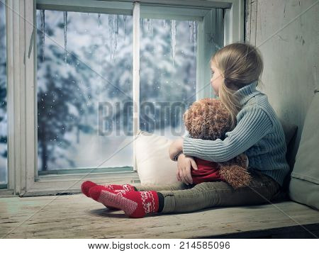 Little girl looking out the window. Outside the winter snow. A wide window sill. A child hugs a plush bear