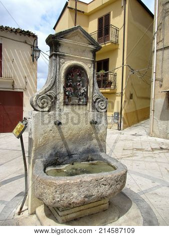 an old foutain on a village square in spain