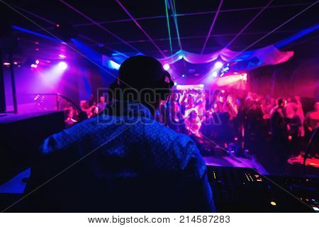 silhouette of a DJ from back in the headphones playing in a nightclub with a crowd of people on the dance floor with multicolored light
