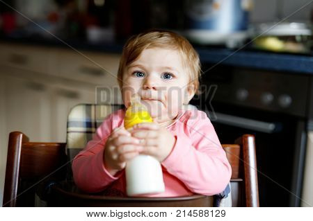 Cute adorable baby girl holding nursing bottle and drinking formula milk. First food for babies. New born child, sitting in chair of domestic kitchen. Healthy babies and bottle-feeding concept.