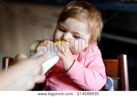 Cute adorable baby girl drinking formula milk. First food for babies from bottle holding by mohter. New born child, sitting in chair of domestic kitchen. Healthy babies and bottle-feeding concept.