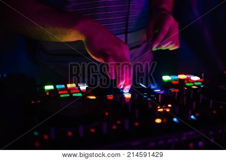 hands on professional DJ mixer with multi-colored glowing buttons mixing music