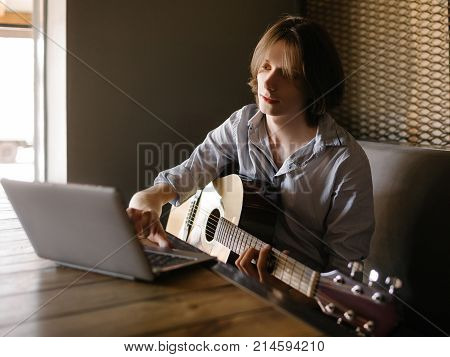 online music school. young man learns how to play guitar through the internet. limitless possibilities for education thanks to modern technologies concept