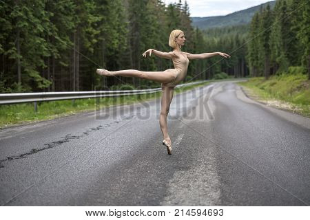 Blonde ballerina stands on the left toe on the roadway on the coniferous forest background. Her arms outstretched to the sides and right leg outstretched backward. She wears beige leotard and pointes.