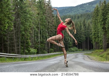 Gorgeous ballerina stands on the right toe on the roadway on the coniferous forest background. Her arms outstretched to the sides, left leg bent in the knee. She wears a red leotard and light pointes.