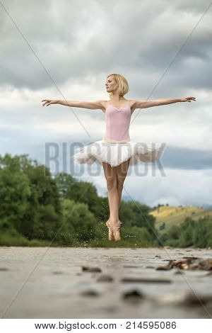 Blonde ballerina jumping with crossed legs in the shallow river on the background of green shore and cloudy sky. She wears white tutu, pink leotard and beige pointes. Her arms elongated to the sides.