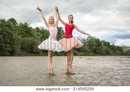 Tender ballerinas stand on the pointes in the shallow river on the background of green shore and cloudy sky. They wear leotards, tutus and ballet shoes. Girls holds their hands together. Horizontal.