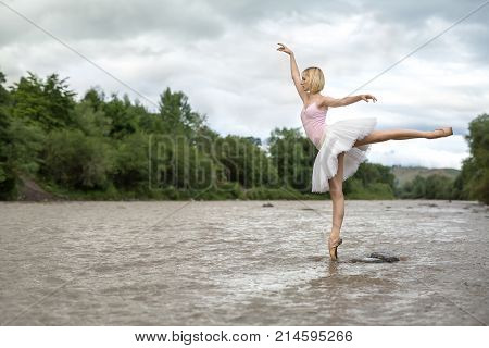 Elegant ballerina stands on the right toe with outstretched arms in the shallow river on the background of green shore and cloudy sky. She wears a white tutu, pink leotard and beige ballet shoes.