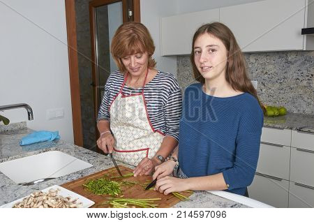 Mother and her teenage daughter are cooking together in the kitchen prepare asparagus. Vegan Family.