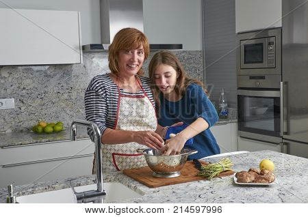 Mother and her teenage daughter are cooking together in the kitchen prepare mushrooms. Vegan Family