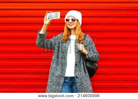 Fashion Young Woman Takes A Picture Self Portrait On A Smartphone On Red Background