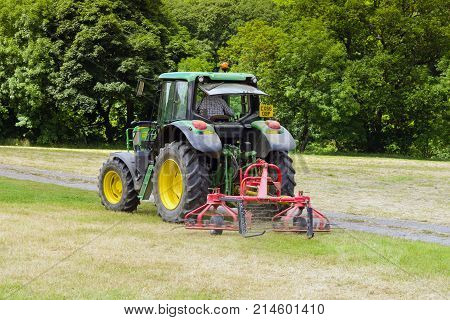 Llangollen Wales UK - July 5 2017: Tractor working in a field with a twin rotor hay turner or tedder attachment a device for turning cut grass or hay