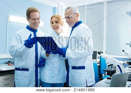 Great analysis results. Cheerful professional biologists smiling and discussing gene analysis results while being in the lab