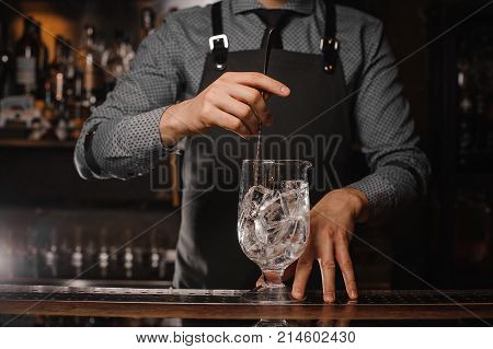 Barman in the apron stirring ice cubes in a large cocktail glass with help of spoon on the bar counter