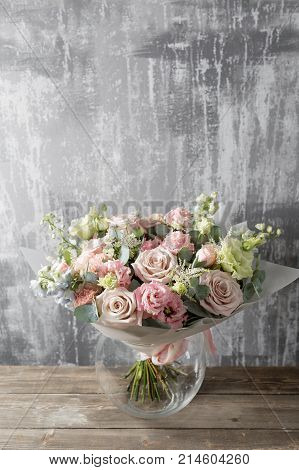 beautiful bouquet of mixed flowers into a vase on wooden table. Bouquet from cultivated flowers in a jug.