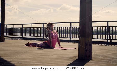 Attractive woman doing yoga exercises on the river bank against sky. Surya namaskar. Kapotasana
