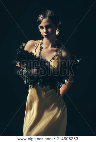 Look and retro style pinup. Pin up pretty fashion model pose on black background. Girl in fashionable yellow dress boa fur. Beauty and vintage fashion. Woman with stylish retro hair and makeup.