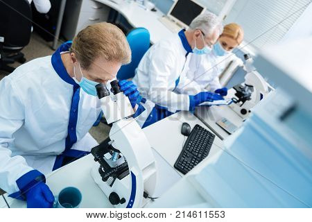 Investigating chromosomes. Serious concentrated researcher of middle age wearing a uniform and a medical face mask and gloves and looking in the microscope