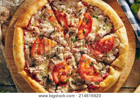 Pizza Restaurant Menu - Delicious Fresh Pizza with Mushrooms, Tomatoes and Meat. Pizza on Rustic Wooden Table with Ingredients