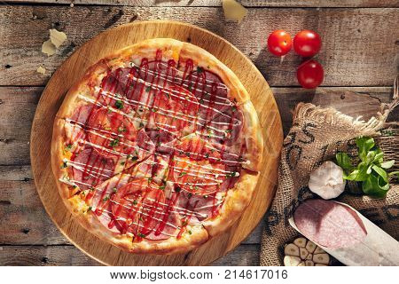 Pizza Restaurant Menu - Delicious Fresh Pizza with Sausage and Tomatoes. Pizza on Rustic Wooden Table with Ingredients