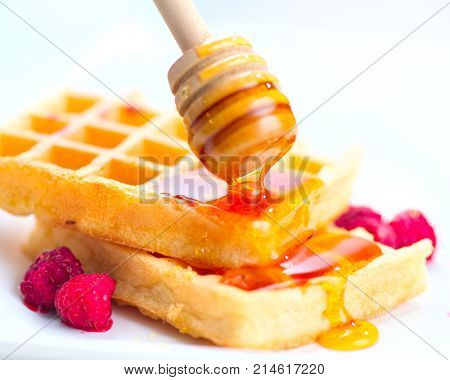 Waffles with honey and berries close-up. Healthy breakfast. Honey pouring on a fresh Belgian waffles