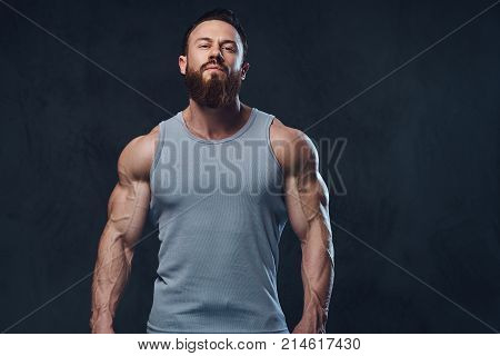 Portrait of brutal bearded bodybuilder dressed in a sleeveless shirt isolated on grey background.
