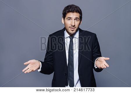 Emotional businessman pulls his hands apart, expressing surprise and disappointment. Business concept.