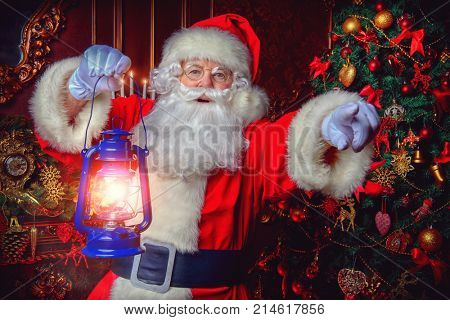 Christmas concept. Portrait of a fairytale Santa Claus standing with lantern and wonders. Beautiful home decorated for Christmas. Time of miracles.