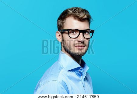 Elegant man in glasses over blue background. Optics style for men. Handsome businessman in spectacles. Male beauty, fashion.