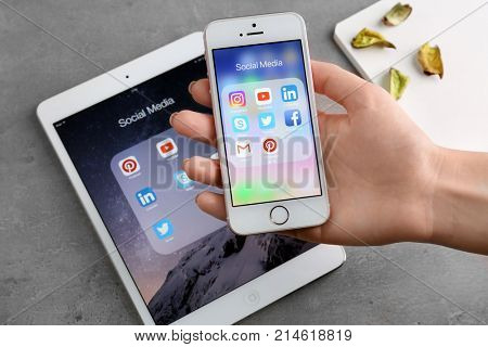 KIEV, UKRAINE - OCTOBER 03, 2017: Woman with iPhone SE displaying social media icons near iPad mini 4 on table