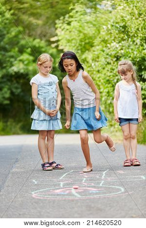 Group of girls play chalk hopscotch for good skills training