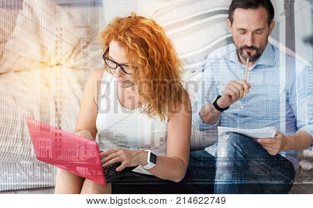 Concentrated couple. Serious clever busy woman looking concentrated while working on the laptop with her attentive handsome boyfriends sitting behind her and making notes