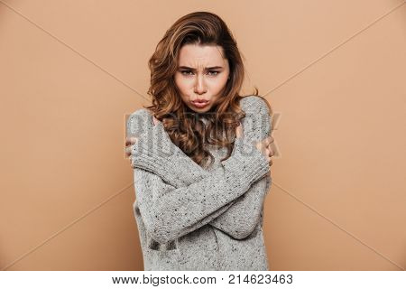 Close-up photo of pretty frozen girl holding her shoulders and looking at camera, isolated on beige background