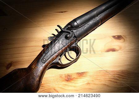 Ancient hunting shotgun closeup on wooden board under light beam