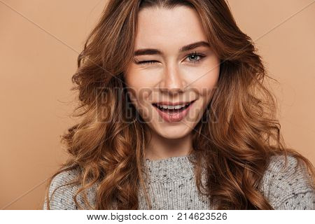 Close-up photo of young charming brunette woman blinks one eye and looking at camera, isolated over beige background