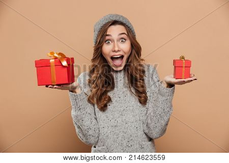 Young charming happy exited girl in winter hat and knitted sweater holding two gift boxes, looking at camera, isolated on beige background