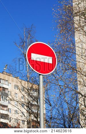 Ban road sign in city against blue sky background