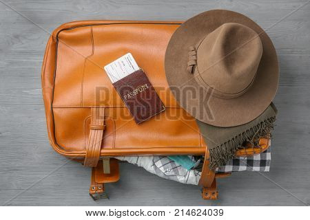 Leather suitcase and passport with ticket on grey background