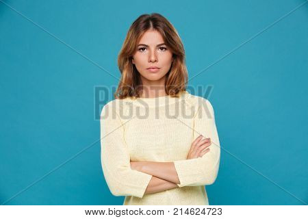 Photo of serious young woman standing isolated over blue wall. Looking camera with arms crossed.