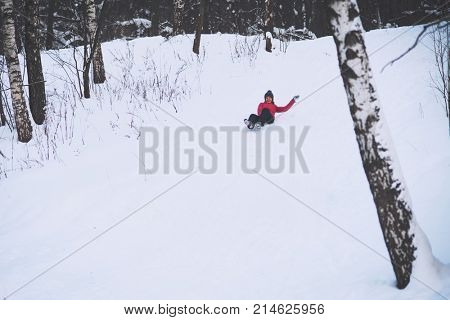 Cheerful young woman riding a sled downhill on a snow covered sledge trail in a white winter forest