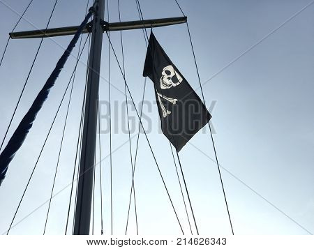 Pirate skull and crossbones Jolly Roger flag flying on a ships mast against a blue sky.