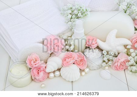 Bathroom beauty treatment cleansing products with carnation flowers, ex foliating salt, soap seashells moisturising cream, body lotion, sponges and wash cloths on white wood background.