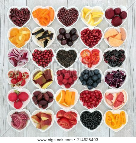 Healthy eating super food to promote good health with fruit, vegetables, grains and pulses in heart shaped bowls on rustic wood background. High in anthocyanins, antioxidants, minerals and vitamins.
