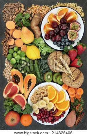 Healthy high fibre dietary food concept including fruit, vegetables, legumes, nuts, whole wheat pasta and whole grain bread rolls. High in antioxidants, omega 3 and vitamins.