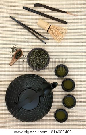 Japanese sencha sukiyu makoto green tea ceremony with teapot and cups, tea leaves, whisk, stick stirrers and tongs on bamboo background.