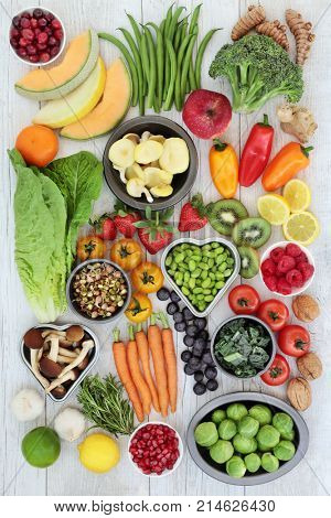 Superfood nutrition concept for healthy eating with foods of fruit, vegetables, nuts, herbs and spice high in antioxidants, anthocyanins, fiber, vitamins and minerals.