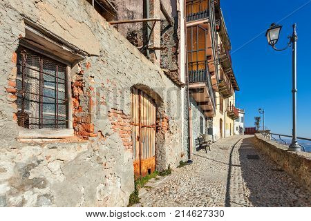 Narrow cobblestone street along old houses and lampposts under blue sky in small town of La Morra in Piedmont, Northern Italy.