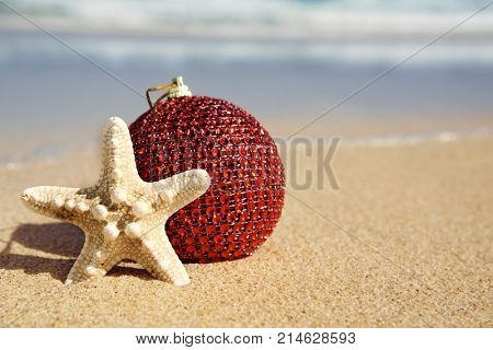 closeup of an elegant red christmas ball and a starfish in the sand of a beach, next to the seashore