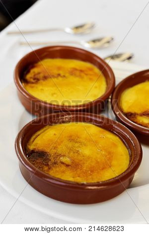 some earthenware bowls with crema catalana, typical creme brulee of Catalonia, Spain, on a table