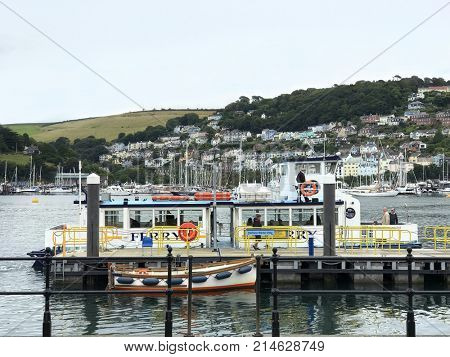 Dartmouth, Devon, UK. 30th August 2017. Dartmouth leisure ferry boat cruiser docked at the quay in Dartmouth harbour with sailing boats to the rear and the quaint town of Darthaven on a hillside.